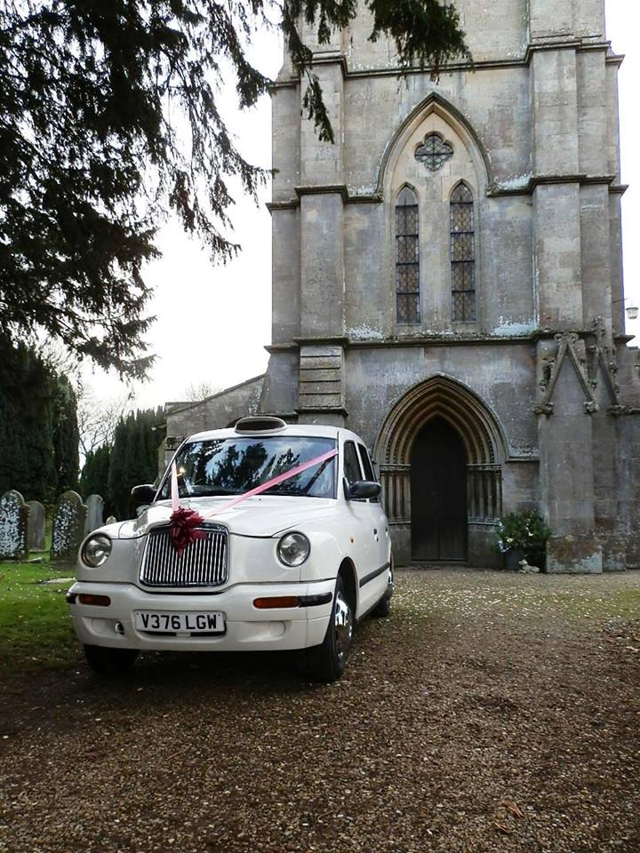 Classic pose of the White Taxi Wedding Car outside a church in Mansfield