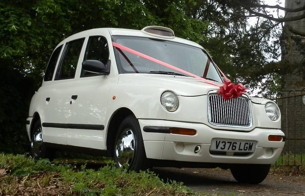 Classic pose of the White Taxi Wedding Car in Leicester